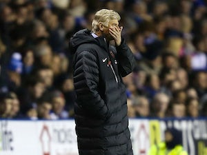 A shocked Arsene Wenger holds his hand to his mouth