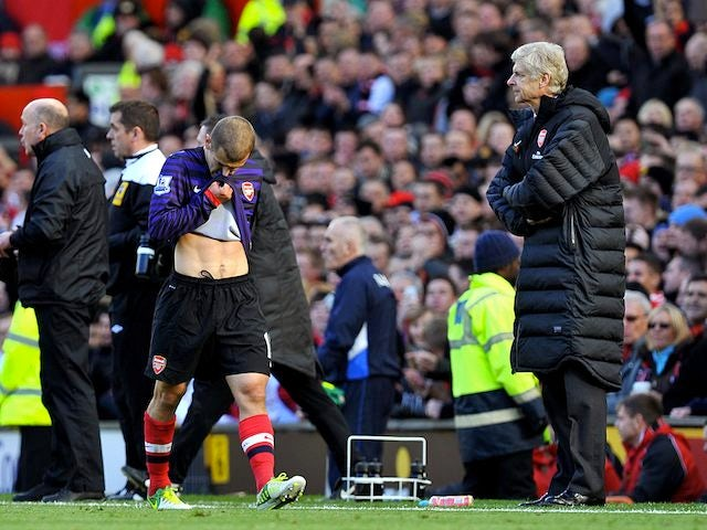 Jack Wilshere walks off the pitch while being eyed by Arsene Wenger