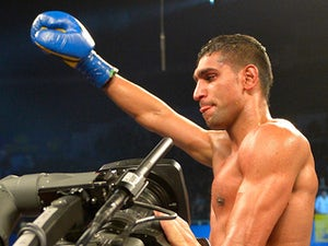 Amir Khan celebrates after stopping Carlos Molina in round 10 on December 15, 2012