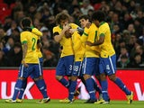 Teammates congratulate Brazil player Fred after scoring against England on February 6, 2013