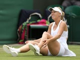 Denmark's Caroline Wozniacki holds her ankle after slipping during her match against Czech Republic's Petra Cetkovska during day three of the Wimbledon Championships on June 26, 2013