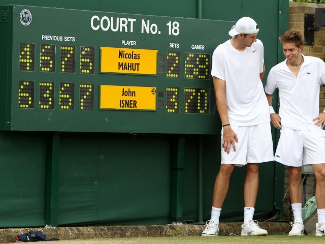 John Isner and Nicolas Mahut stand in front of the scoreboard at Wimbledon.