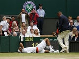 Argentina's Juan Martin Del Potro rolls on the ground in pain during his match against Spain's David Ferrer during day nine of the Wimbledon Tennis Championships on July 3, 2013