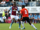 Aston Villa's Christian Benteke and Luton Town's Solomon Taiwo battle for the ball during a friendly match on July 23, 2013