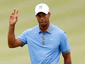 Tiger Woods gestures after holing a putt at Firestone CC on August 2, 2013
