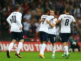 Theo Walcott of England celebrates with team-mate Tom Cleverley of England after scoring a goal during the International Friendly match between England and Scotland at Wembley Stadium on August 14, 2013