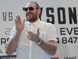 Heavyweight boxer Tyson Fury claps during a press conference on July 11, 2013