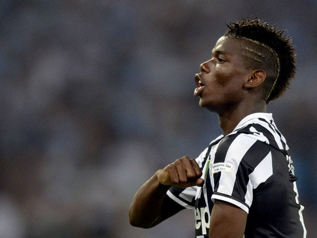 Paul Pogba of FC Juventus celebrates scoring the first goalduring the TIM Supercup match between SS Lazio and FC Juventus at Olimpico Stadium on August 18, 2013