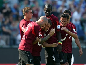 Hannover's Szabolcs Huszti is congratulated by team mates after scoring the opening goal against Schalke on August 24, 2013