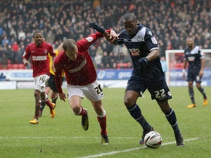 Chris Solly of Charlton Athletic tries to tackle Dany N'Guessan of Millwall during the npower Championship match between Charlton Athletic and Millwall at The Valley on March 16, 2013