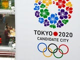 People walk under the bid emblem of the Tokyo 2020 Olympic and Paralympic Games hoisted in downtown Tokyo on September 7, 2013