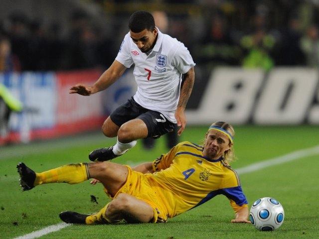 Anatoliy Tymoshchuk performs a slide tackle on England winger Aaron Lennon.