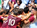 Roma's Federico Balzaretti is mobbed by teammates after scoring the opening goal against Lazio during their Serie A match on September 22, 2013