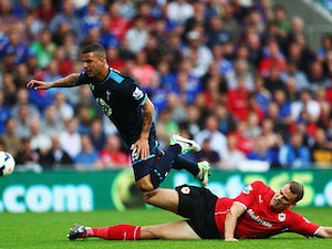 Tottenham's Kyle Walker is tackled by Cardiff's Ben Turner during their Premier League match on September 22, 2013
