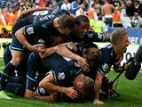 Spurs players pile on top of Paulinho following his last minute winner against Cardiff City on September 22, 2013