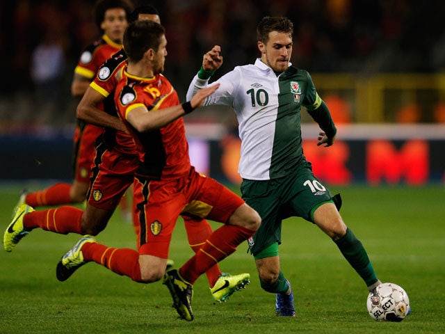 Sebastien Pocognoli of Belgium is beaten by Aaron Ramsey of Wales during the FIFA 2014 World Cup Qualifying Group A match between Belgium and Wales at King Baudouin Stadium on October 15, 2013