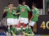 Saint Etienne's French midfielder Romain Hamouma is congratulated by his teammates after scoring a goal during the French L1 football match Saint-Etienne (ASSE) vs Paris (PSG) on October 27, 2013