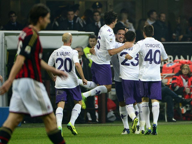 Fiorentina's midfielder Juan Manuel Vargas of Peru celebrates with teammates after scoring a free kick during the Italian serie A football match AC Milan vs Fiorentina, on November 2, 2013