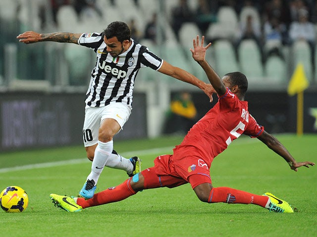 Juventus' Carlos Tevez and Catania's German Rolin battle for the ball on October 30, 2013