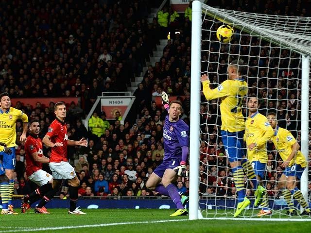 Man United's Robin van Persie heads in the opening goal against Arsenal on November 10, 2013