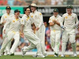 Mitchell Johnson of Australia celebrates with Michael Clarke after dismissing Joe Root of England during day two of the First Ashes Test match between Australia and England at The Gabba on November 22, 2013