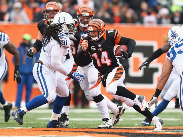 Andy Dalton #14 of the Cincinnati Bengals runs with the ball during the NFL game against the Indianapolis Colts at Paul Brown Stadium on December 8, 2013