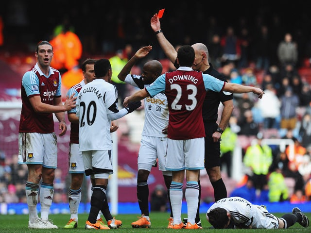 Andy Carroll of West Ham United is sent off by referee Howard Webb after a clash with Chico Flores of Swansea City (R) during the Barclays Premier League match between West Ham United and Swansea City at Boleyn Ground on February 1, 2014