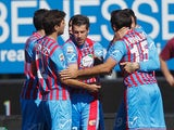 Catania's Mariano Izco celebrates with teammates after scoring his team's opening goal against Lazio in their Serie A match on February 16, 2014