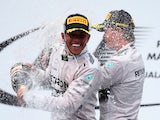 Lewis Hamilton of Great Britain and Mercedes GP (L) celebrates on the podium with second placed Nico Rosberg of Germany and Mercedes GP after the Malaysian Grand Prix on March 30, 2014