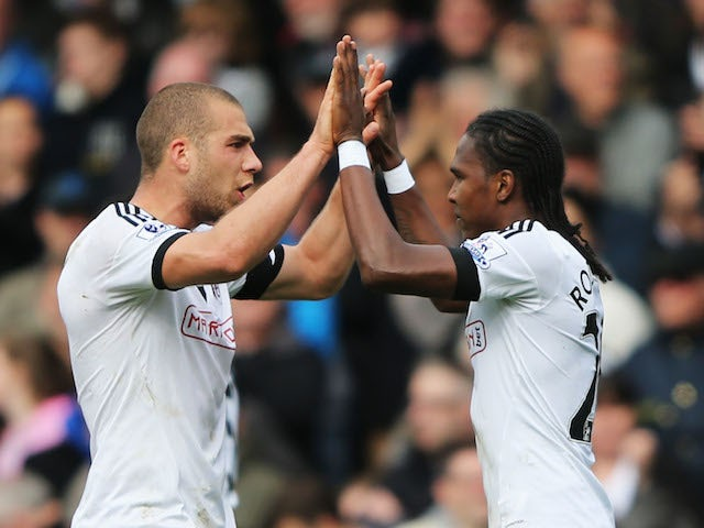 Hugo Rodallega of Fulham (R) celebrates with Pajtim Kasami as he scores their first goal during the Barclays Premier League match against Norwich on April 12, 2014
