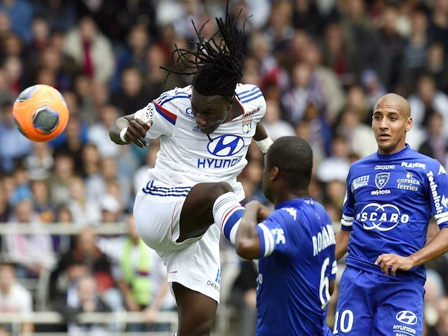 Lyon's French forward Bafetimbi Gomis (L) heads the ball and scores despite Bastia's Ivory Coast midfielder Romaric N Dri Koffi (C) and Bastia's Tunisian midfielder Wahbi Khazri during a match on April 27, 2014