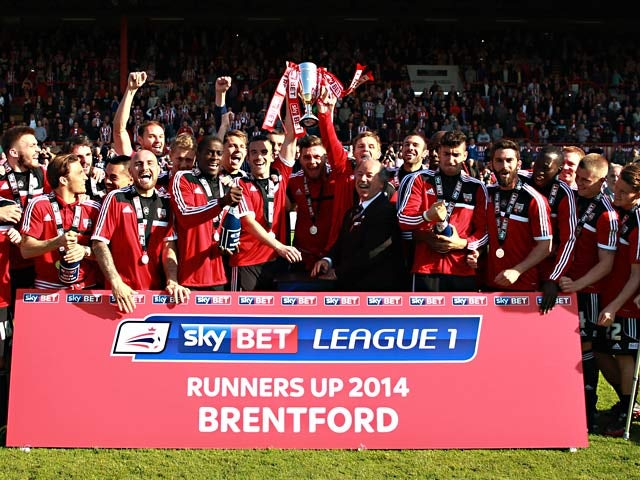 Brentford players and staff celebrates with the trophy as League One runner-ups after their final League One match on May 3, 2014