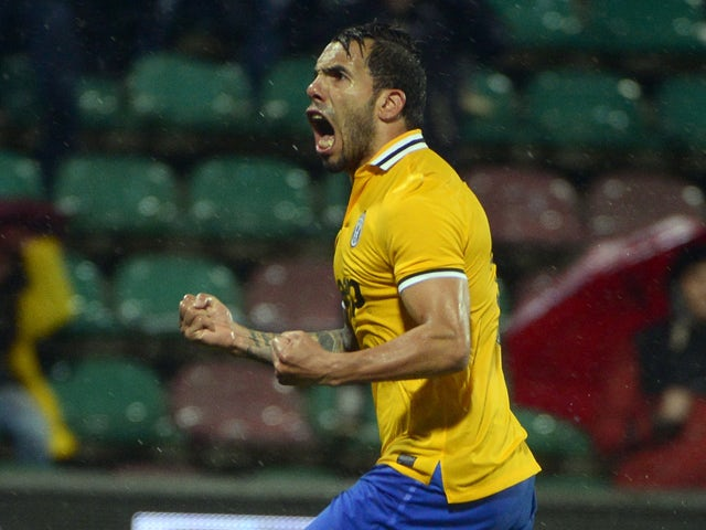 Juventus' Argentinian forward Carlos Alberto Tevez celebrates after scoring during the Italian Serie A football match between Sassuolo and Juventus, on April 28, 2014
