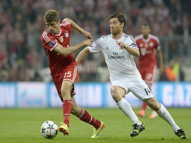 Bayern Munich's midfielder Thomas Mueller and Real Madrid's midfielder Xabi Alonso fight for the ball during the UEFA Champions League second-leg semi-final football match on April 29, 2014
