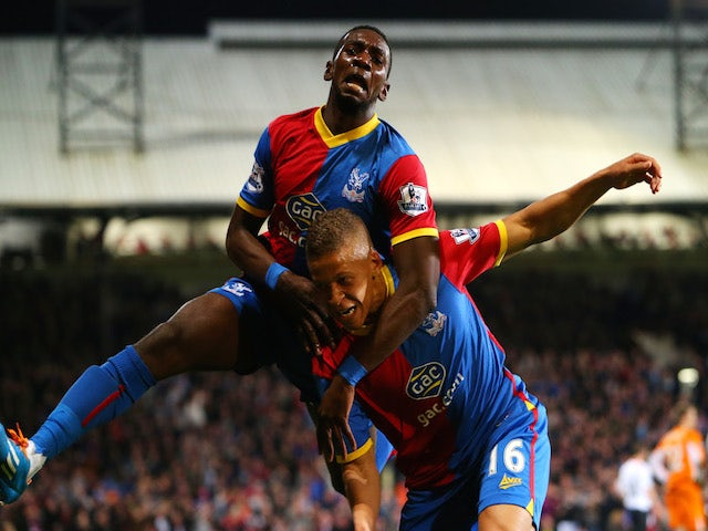 Dwight Gayle #16 (R) of Crystal Palace celebrates with teammate Yannick Bolasie after scoring his team's third goal to level the scores at 3-3 against Liverpool on May 5, 2014