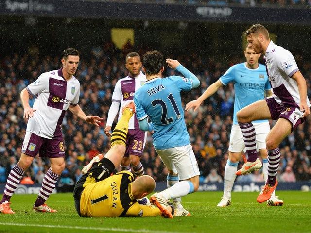 Goalkeeper Brad Guzan of Aston Villa makes a save from David Silva of Manchester City during the Barclays Premier League match between Manchester City and Aston Villa at Etihad Stadium on May 7, 2014