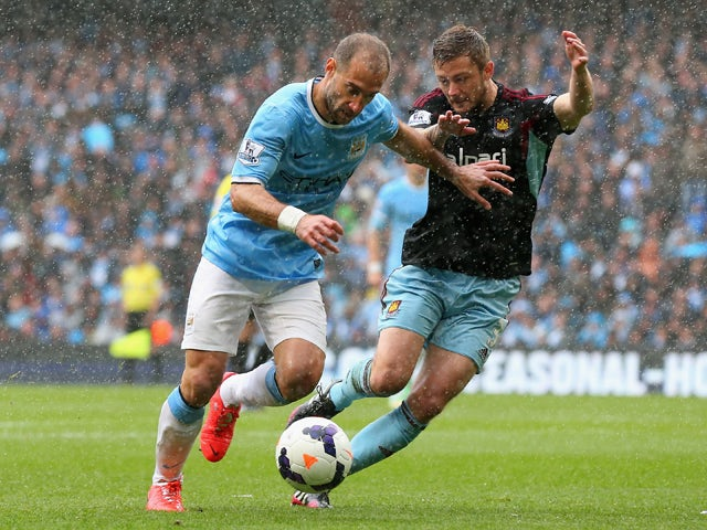 Pablo Zabaleta of Manchester City holds off George McCartney of West Ham United during the Barclays Premier League match between Manchester City and West Ham United at the Etihad Stadium on May 11, 2014