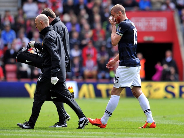Manchester United's Serbian defender Nemanja Vidic walks off to get treated for a bloody nose during during the English Premier League football match between Southampton and Manchester United at St Mary's stadium in in Southampton on May 11, 2014