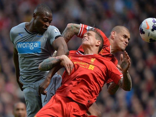 Newcastle United's Nigerian striker Shola Ameobi (L) challenges Liverpool's Danish defender Daniel Agger (C) and Liverpool's Slovakian defender Martin Skrtel on May 11, 2014