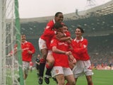 Eric Cantona is mobbed by his Manchester United teammates after scoring against Chelsea in the FA Cup final on May 14, 1994.