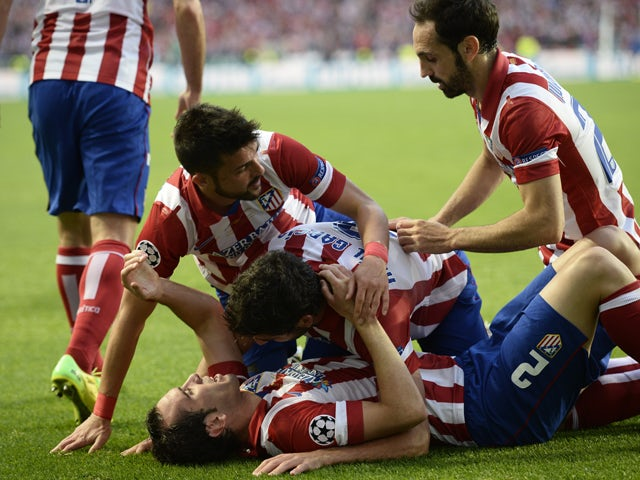 Atletico Madrid's players celebrate after scoring during the UEFA Champions League Final Real Madrid vs Atletico de Madrid at Luz stadium in Lisbon, on May 24, 2014