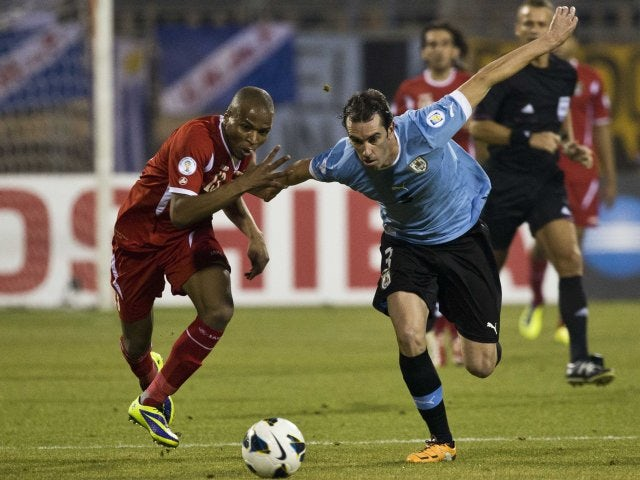 Uruguay defender Diego Godin battles for possession on November 13, 2013.