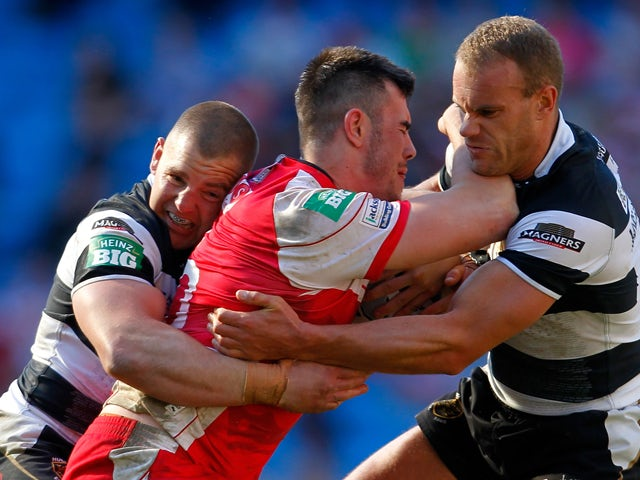 Jordan Cox of Hull KR is tackled by Mark O'Meley and Daniel Holdsworth of Hull FC during the Super League Magic Weekend match between Hull FC and Hull Kingston Rovers at the Etihad Stadium on May 25, 2013