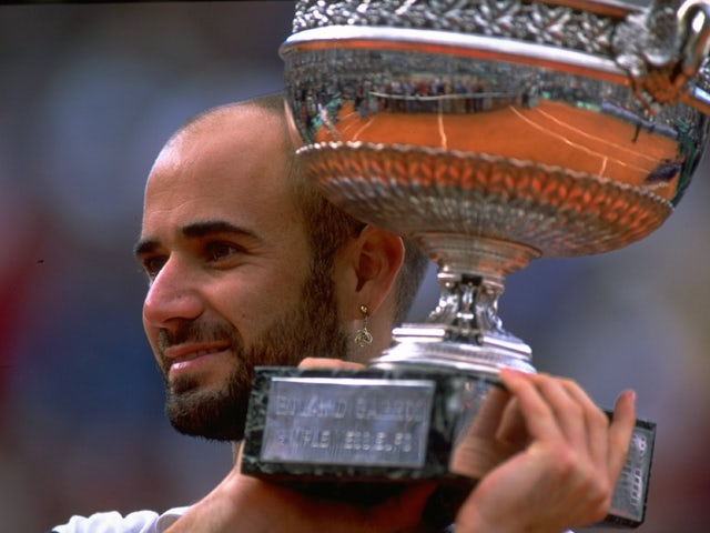 Andre Agassi of the United States celebrates victory with the trophy during the 1999 French Open Final match against Andrei Medvedev on June 6, 1999