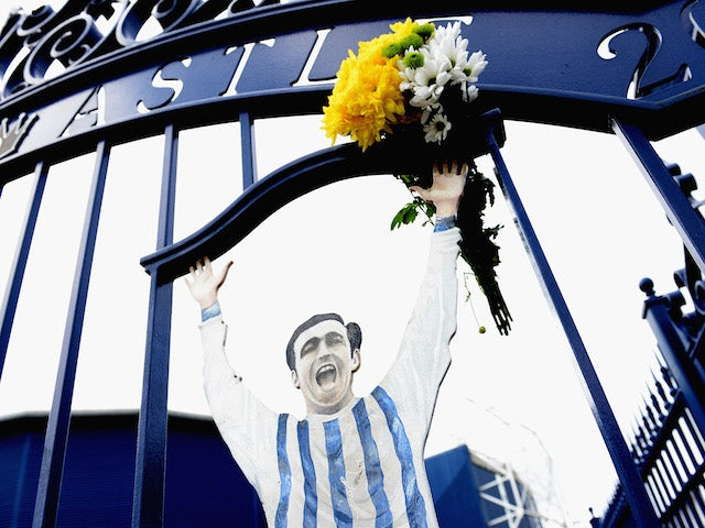 Fans pose in front of the Jeff Astle Gates before the Barclays Premier League match between West Bromwich Albion and Stoke City at The Hawthorns on May 11, 2014