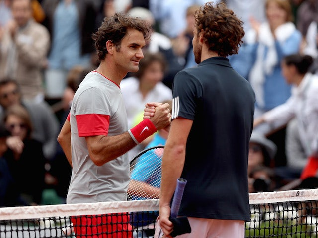 Roger Federer and Ernests Gulbis shake hands at the net after the latter's victory in the French Open on June 1, 2014