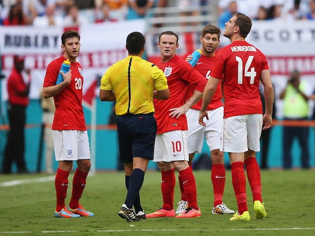 Wayne Rooney of England (C) speaks to referee Ricardo Salazar as Adam Lallana (L), Steven Gerrard (2nd R) and Jordan Henderson (R) look on as Salazar delays the match due to a storm on June 7, 2014