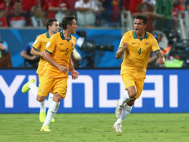 Tim Cahill of Australia celebrates scoring his teams first goal with teammate Mark Milligan during the 2014 FIFA World Cup Brazil Group B match between Chile and Australia at Arena Pantanal on June 13, 2014