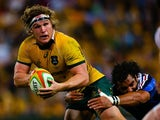 Australian flanker Michael Hooper is tackled by French wing Yoann Huget during the first rugby union test match against France at Suncorp Stadium in Brisbane on June 7, 2014