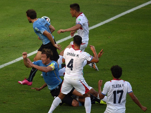 Uruguay's defender Diego Lugano falls after being brought down by Costa Rica's defender Junior Diaz during a Group D football match between Uruguay and Costa Rica at the Castelao Stadium in Fortaleza during the 2014 FIFA World Cup on June 14, 2014